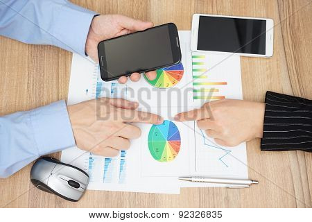Top View Of Business People Analyzing Sales Report And  Reading Information On Mobile Phone