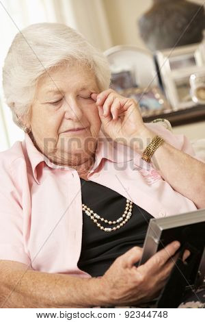 Unhappy Retired Senior Woman Sitting On Sofa At Home Looking At Photograph