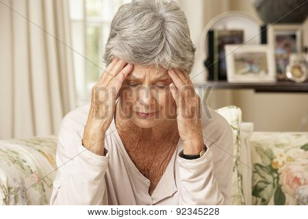 Unhappy Retired Senior Woman Sitting On Sofa At Home