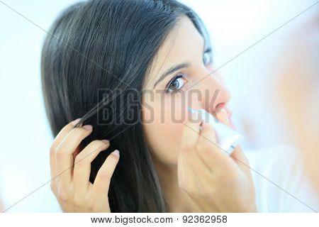 Beautiful brunette woman applying concealer
