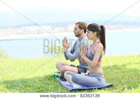Couple doing meditation and yoga exercises in outdoor park