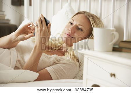 Woman In Bed At Home Texting On Mobile Phone