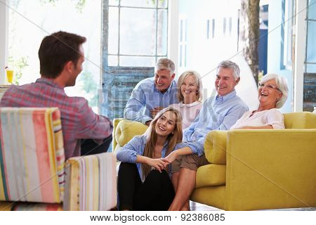 Extended Family Group At Home Relaxing In Lounge