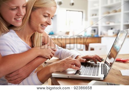 Girl hugging her mother, working on laptop at home