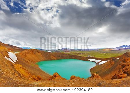 Summer in Iceland. Picturesque lake in the crater of an extinct volcano. Lake water bright green color. On the shores lie snowfields from last year