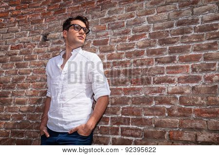 Young casual man holding his hands in pockets while leaning on a brick wall, lloking away from the camera.