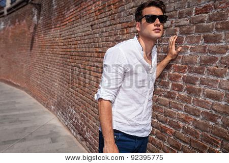 Young handsome fashion man leaning with his hand on a brick wall while looking away from the camera.