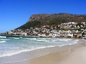 A view across False Bay beach on the Cape penninsula of South Africa shows buildings of the town Fish Hoek in the distance poster