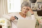 Frustrated Retired Senior Woman Sitting On Sofa At Home Using Laptop poster