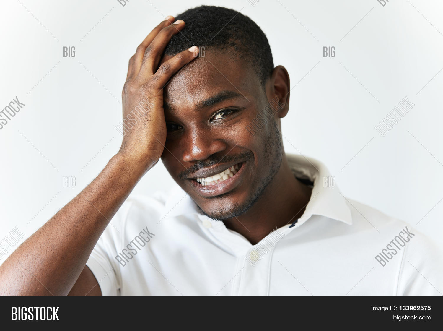 7a98785eb Young handsome African man with healthy skin and short hair-cut wearing  white T-shirt touching his head looking at the camera and smiling with  confused ...