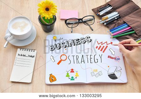 Business hand write white book on desktop and Strategy Concept.