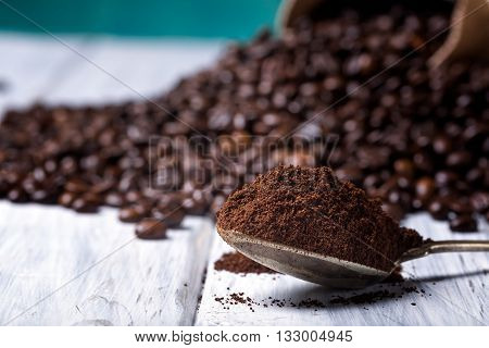Ground Coffee In Spoon With Coffee Beans.