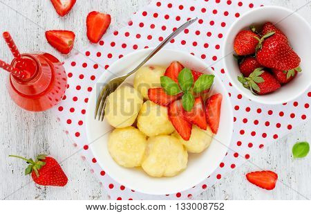 Dumplings with cottage cheese strawberries and basil top view