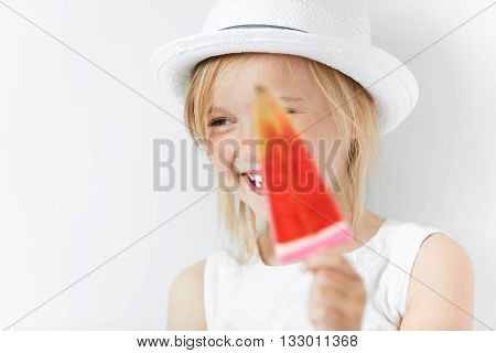 Smiling Caucasian Child Laughing And Hiding Behind Red Popsicle In Her White Beachwear Summer Clothe