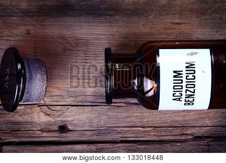 Old chemical bottle with label on wooden background