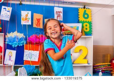 Interior of game room in preschool kindergarten with little girl child. Happy laughing child in preschool class.