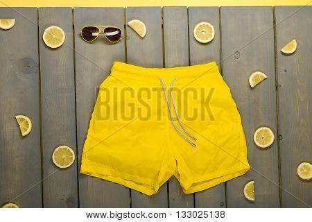 Man Beach Accessories On Wooden Background. Yellow Swim Trunks, Aviator Sunglasses Between Parts Of