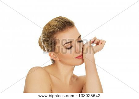 Young woman smelling perfume on her wrist.