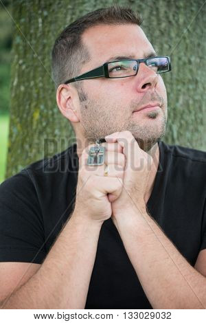 Man praying outside holding a cross, sitting against a tree