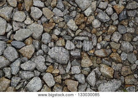 Wet crushed stones of railway ballast and small dry leaves (photo after light rain)