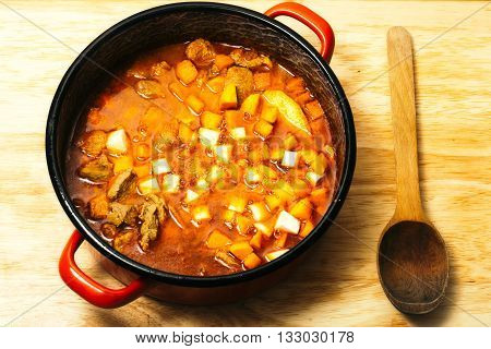 Meat stew with vegetables in red pot with wooden spoon on timber table background