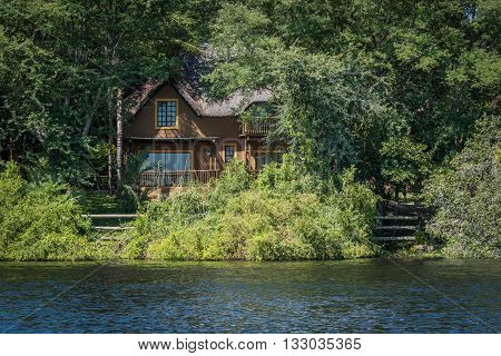 Brown thatched villa in trees on riverbank