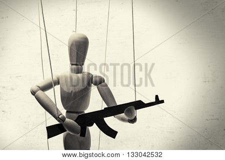A puppet with gun in the hands of the tyrant