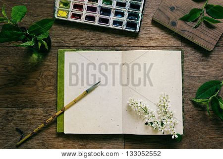 The workplace painter and green leaves. The resentation. The blank notebook. Spring time blank notebook. Background.