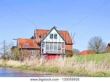 Houses at a river. Sunny day with blue sky and fluffy clouds at a river in northern Germany.