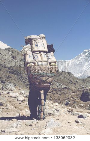 GORAK SHEP, NEPAL - CIRCA MARCH 2010: Rear view of single sherpa tourism guide carrying large bundel of supplies surrounded by rocks and mountains. Gorak Shep (everest trek), Nepal circa March 2010.
