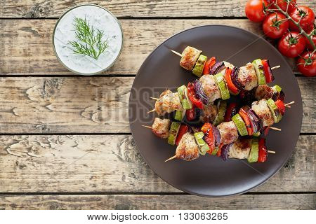 Turkey or chicken meat shish kebab skewers with tzatziki sauce, and tomatoes on rustic wooden table background. Traditional barbecue grill shish food