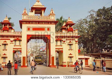 VARANASI, INDIA - JANUARY 3, 2016: People traffic and rushing students walking past the gates of Benaras Hindu University on January 3, 2016. Varanasi urban agglomeration had a population of 1435113