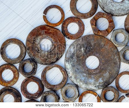 old nuts and washers on wooden white background. Flat lay