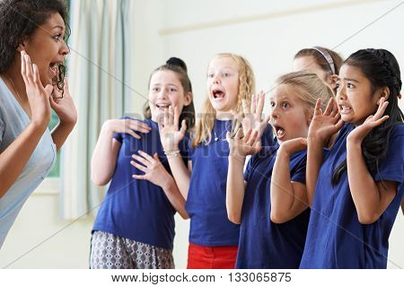 Group Of Children With Teacher Enjoying Drama Class Together