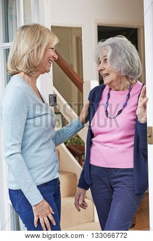 Mature Woman Checking On Elderly Female Neighbor