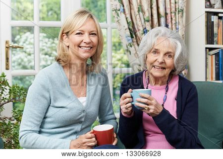 Woman Taking Time To Visit Senior Female Neighbor And Talk