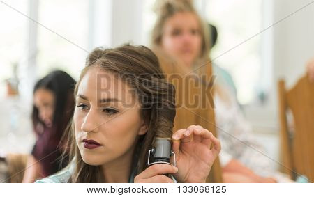 Young attractive woman using a curling iron in a room with other women who prepare for a wedding.