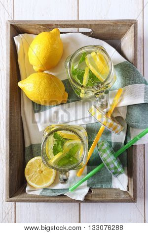 Cool refreshing drink: water lemon and mint on a wooden tray