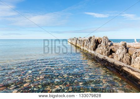 Wood Pilings jut out into Lake Superior at Whitefish Point in the Upper Peninsula of Michigan. Clear lake water reveals the colorful stones under the water
