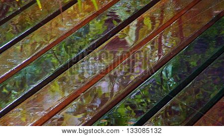 Wet wooden deck with colorful reflection and rain drop
