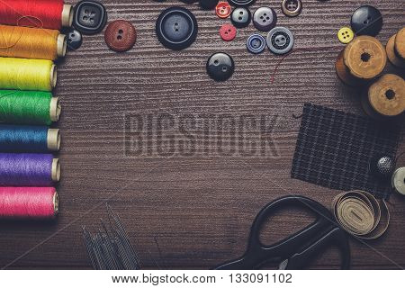 buttons, needles and multicolored threads on the wooden table