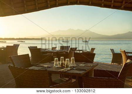 Restaurant and boats on the coast of Gili Travangan island with a sunrise view of Gunung Rinjani volcano on Lombok island, Indonesia. Soft morning light