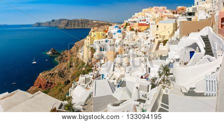 Picturesque panorama of Oia or Ia on the island Santorini, white houses, windmills and church with blue domes, and island Therasia, Greece
