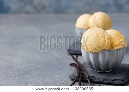 Vanilla Ice Cream with vanilla pods in metal vintage bowl. Homemade Organic product Slate background Copy space