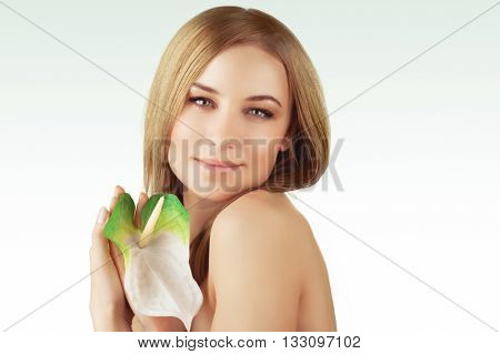 Portrait of a beautiful young woman with calla flower over clean background, healthy lifestyle, beauty treatment, enjoying dayspa
