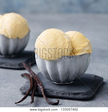 Vanilla Ice Cream with vanilla pods in metal vintage bowl. Homemade Organic product Slate background