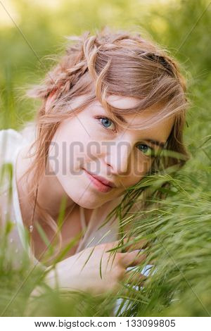 Cute pretty young woman lying on grass outdoors