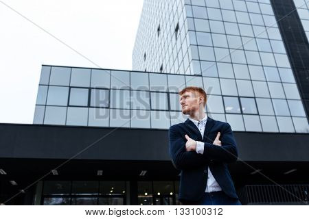 Redhead businessman standing with arms folded outdoors with glass building on background and looking away