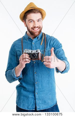 Close-up portrait of a bearded smiling hipster man showing okay sign and holding retro camera isolated on the white background