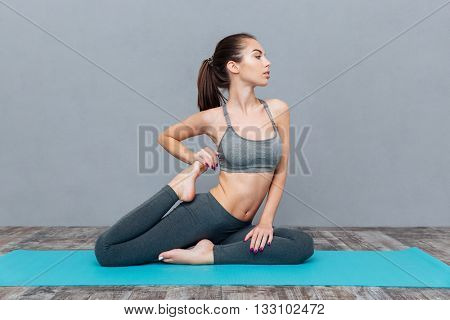 Young woman doing yoga asana Eka Pada Rajakapotasana (one legged king pigeon) isolated on grey background